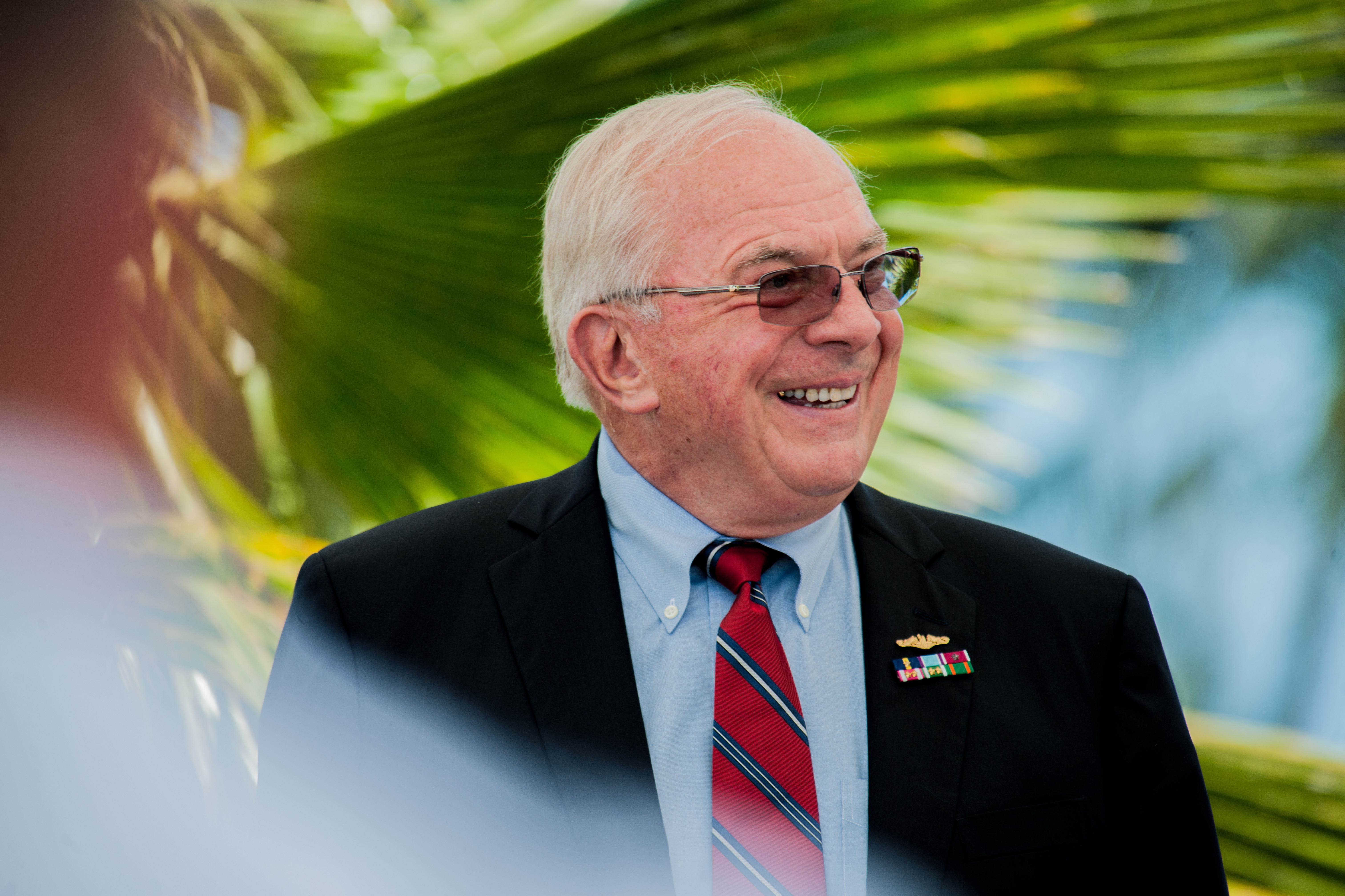 Retired Vice Adm. Albert Konetzni laughs at jokes from his former colleagues describing his historic moments as Pacific Fleet Submarine Force commander during the Konetzni Hall building dedication ceremony held at Commander, Submarine Squadron 15 headquarter