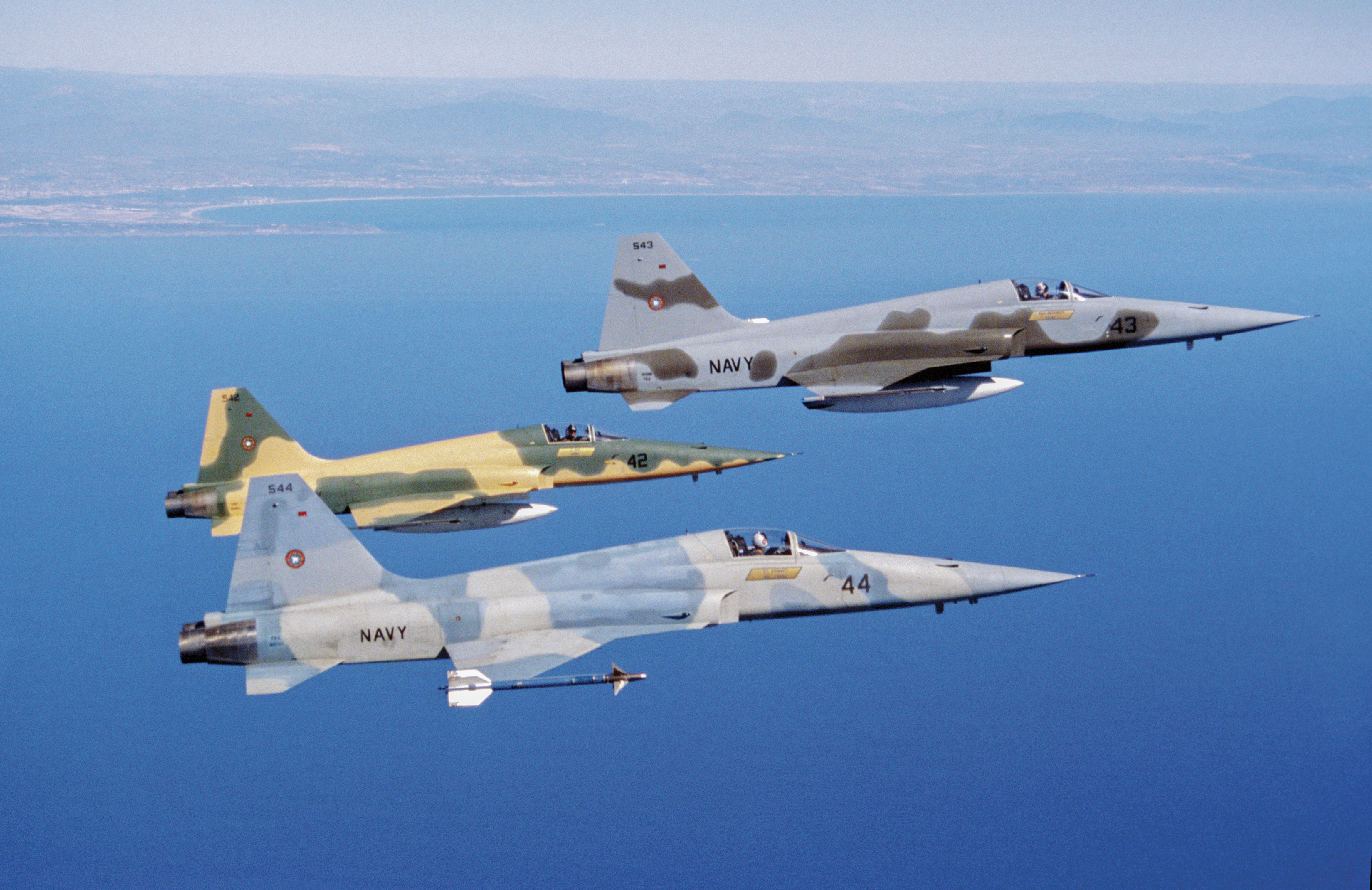Three U.S. Navy F-5 Tiger II adversary aircraft in flight