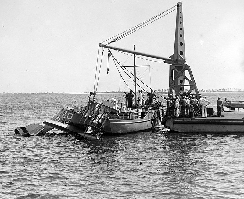 A wreck of a U.S. Navy N-9 training aircraft being hauled in from the water.