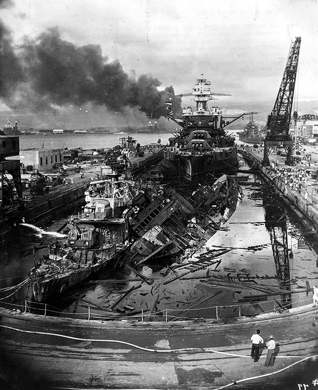 The USS Cassin toppled onto the USS Downes in the flooded drydock at Pearl Harbor, 7 December 1941, with the USS Pennsylvania (BB-38) behind.