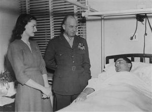 As Broome's wife, Jane, looks on, Lieutenant General Alexander A. Vandegrift, Commandant of the Marine Corps, visits the wounded officer at Bethesda Naval Hospital in January 1945. On the 18th of that month, the major died, leaving behind a son and daught