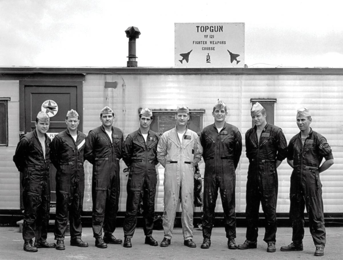 Members of TOPGUN posing in front of a trailer at NAS with sign reading TOPGUN