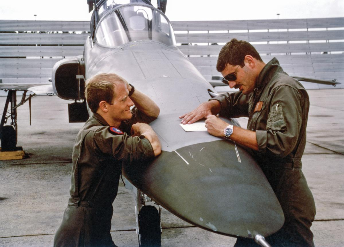 TOPGUN instructors using the nose of an F-5 Tiger II to make notes for the debrief