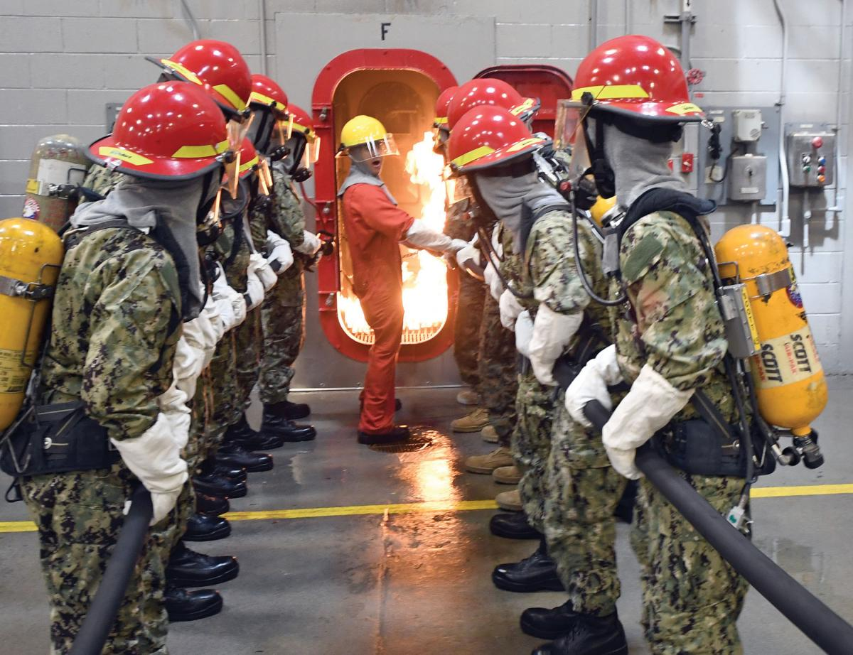 midshipman candidates fight a fire in a simulated shipboard compartment