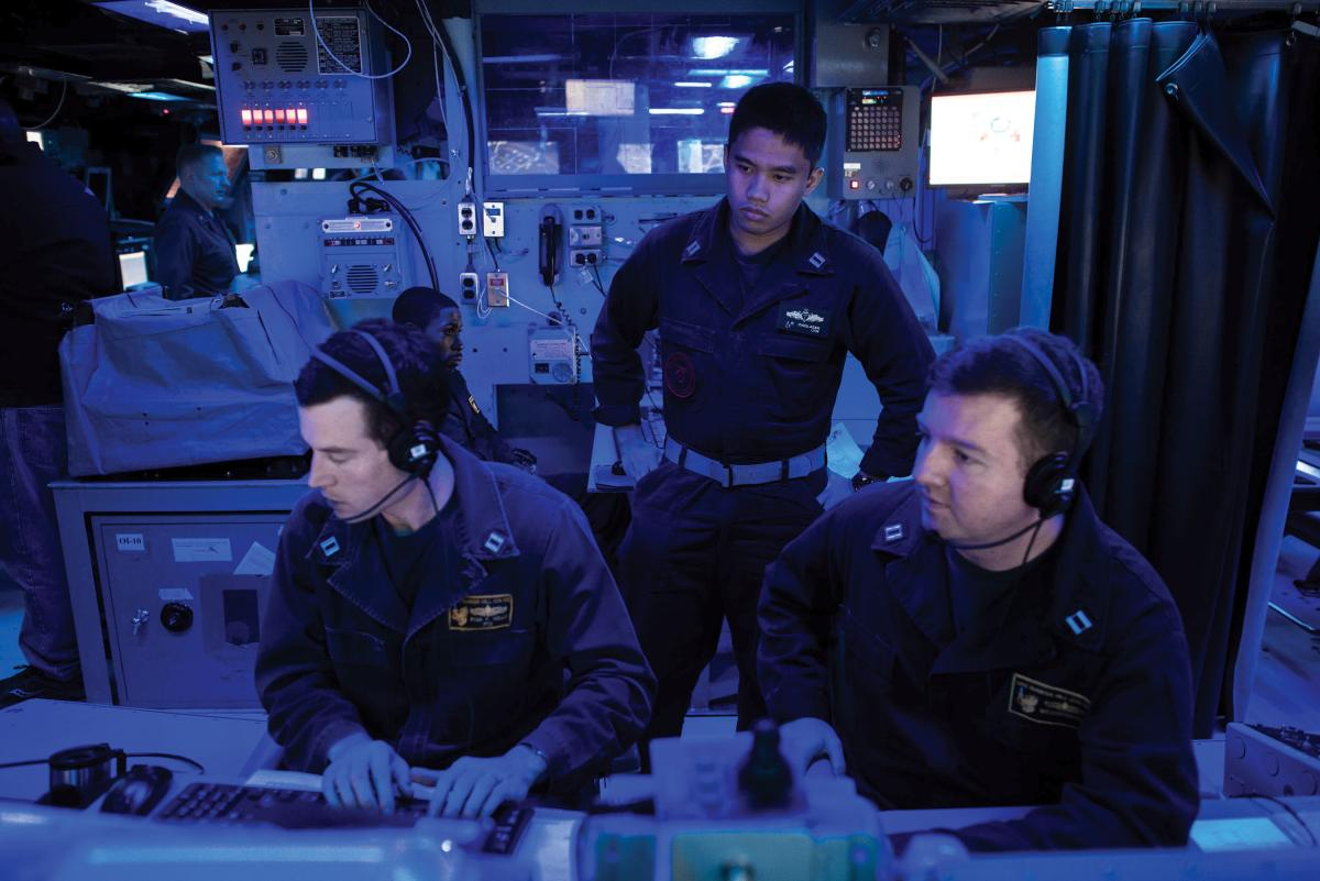 A surface warfare tactics instructor oversees the training of two officers on board the USS Bunker Hill (CG-52).