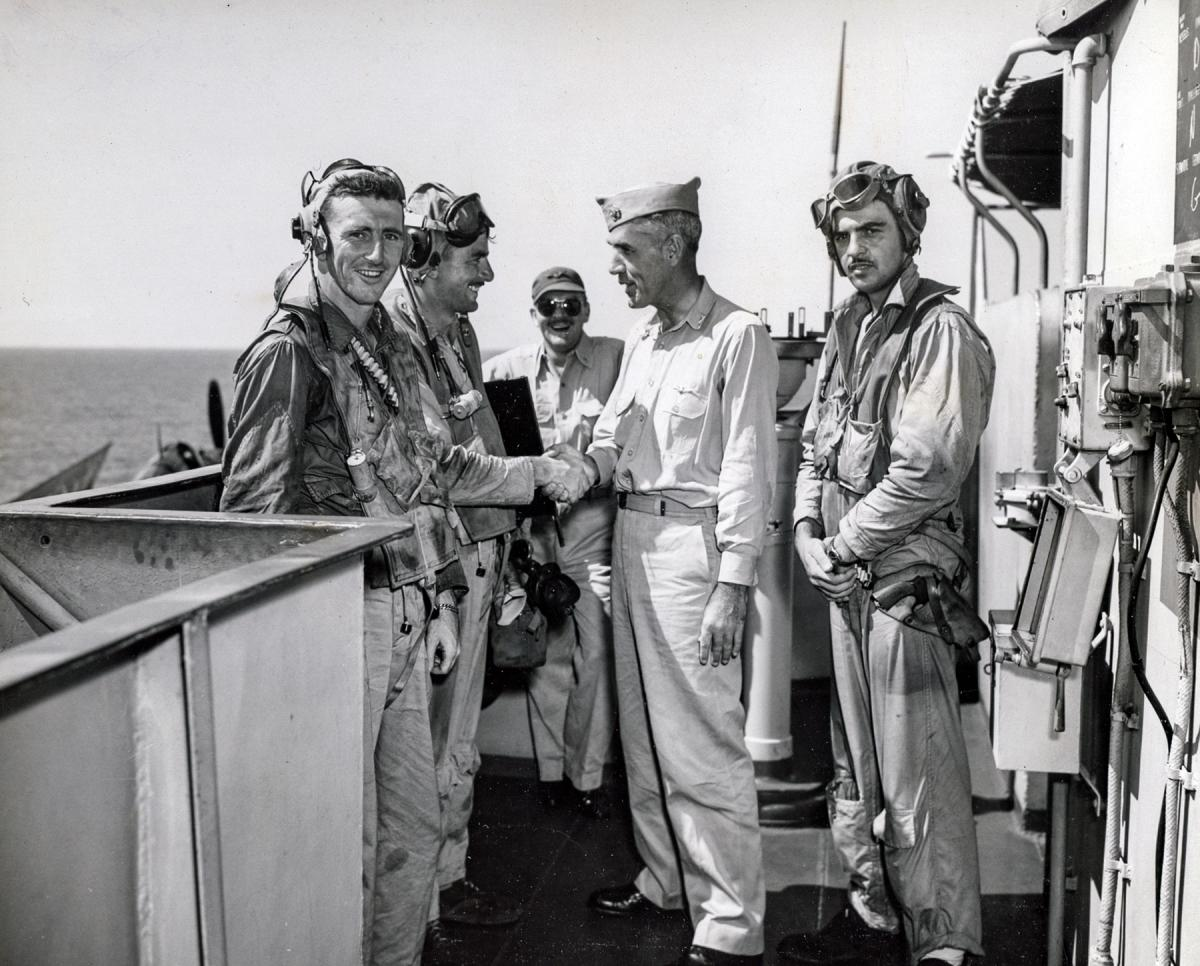 Ensign John Buchanan (left) and Lieutenant Kenneth Hippe are greeted by Captain T. B. Williamson, skipper of the USS Kalinin Bay