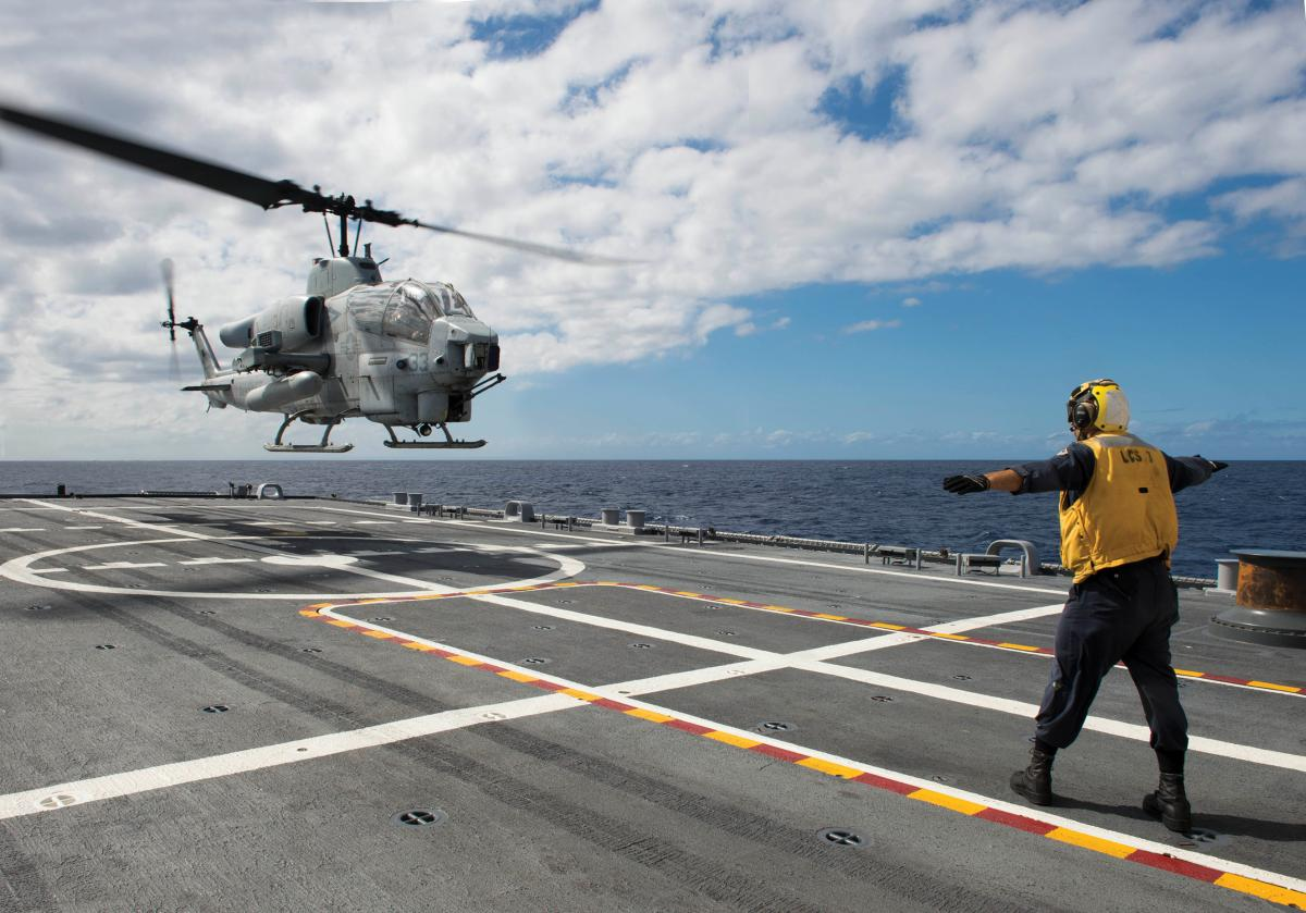 Sailor signals an AH-1 Cobra helicopter from Marine Air Group (MAG) 24 during deck landing qualification training aboard the littoral combat ship USS Fort Worth (LCS-3)