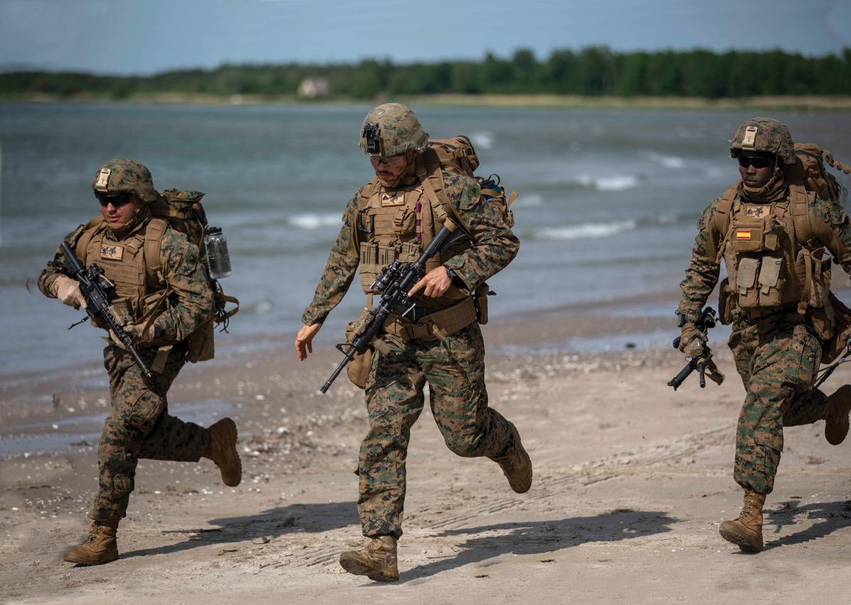 U.S. Infantry Marines sprint after landing on a beach during an amphibious assault exercise