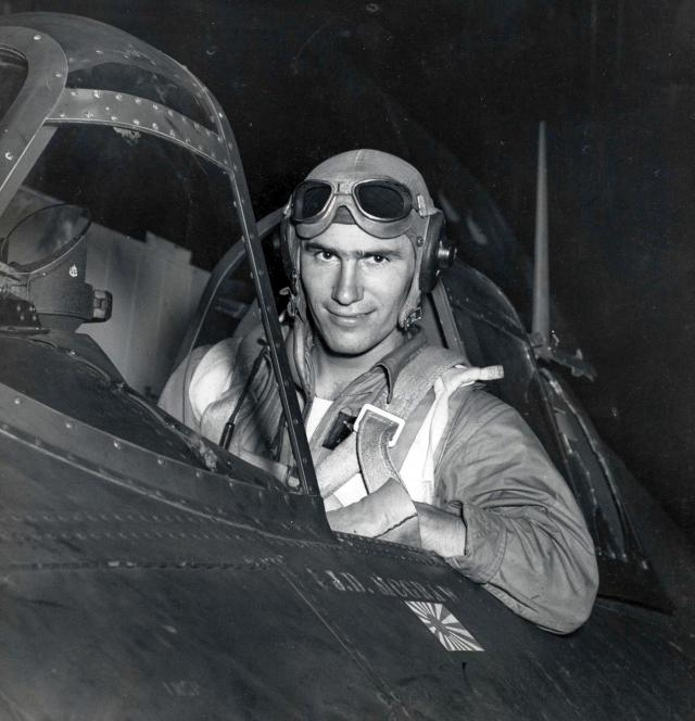 Ensign Joseph McGraw seated in the cockpit of a Wildcat fighter aircraft