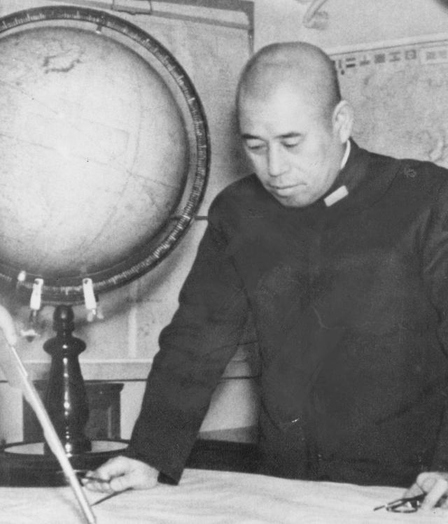 Portrait of Admiral Isoroku Yamomoto looking down at a map.