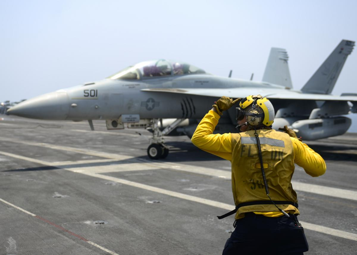 "Aviation Boatswain's mate directs an EA-18G Growler, from the ""Gray Wolves"" of Electronic Attack Squadron (VAQ) 142, on the flight deck of the aircraft carrier USS Nimitz (CVN 68), July 25, 201"