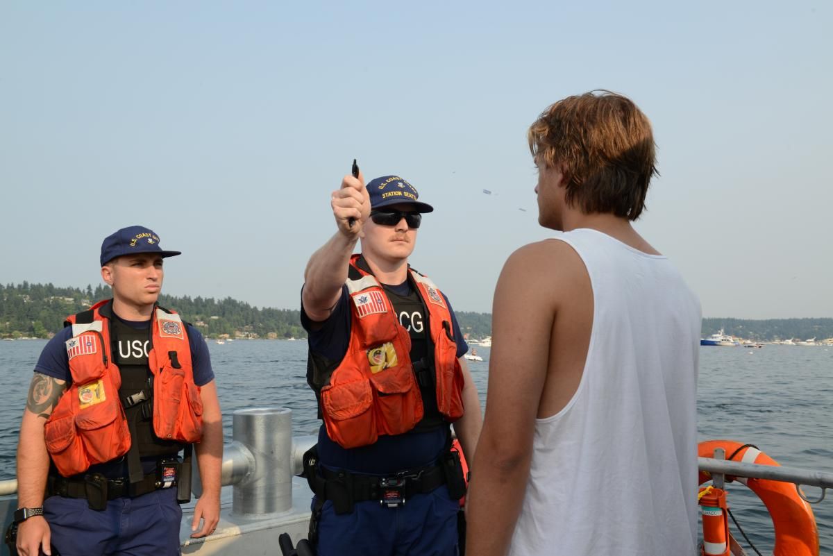 Petty Officer 2nd Drew Allen and Petty Officer 2nd Class Jordan Kuehl perform field sobriety tests on a boater during Seattle's Seafair, 5 August 2017.