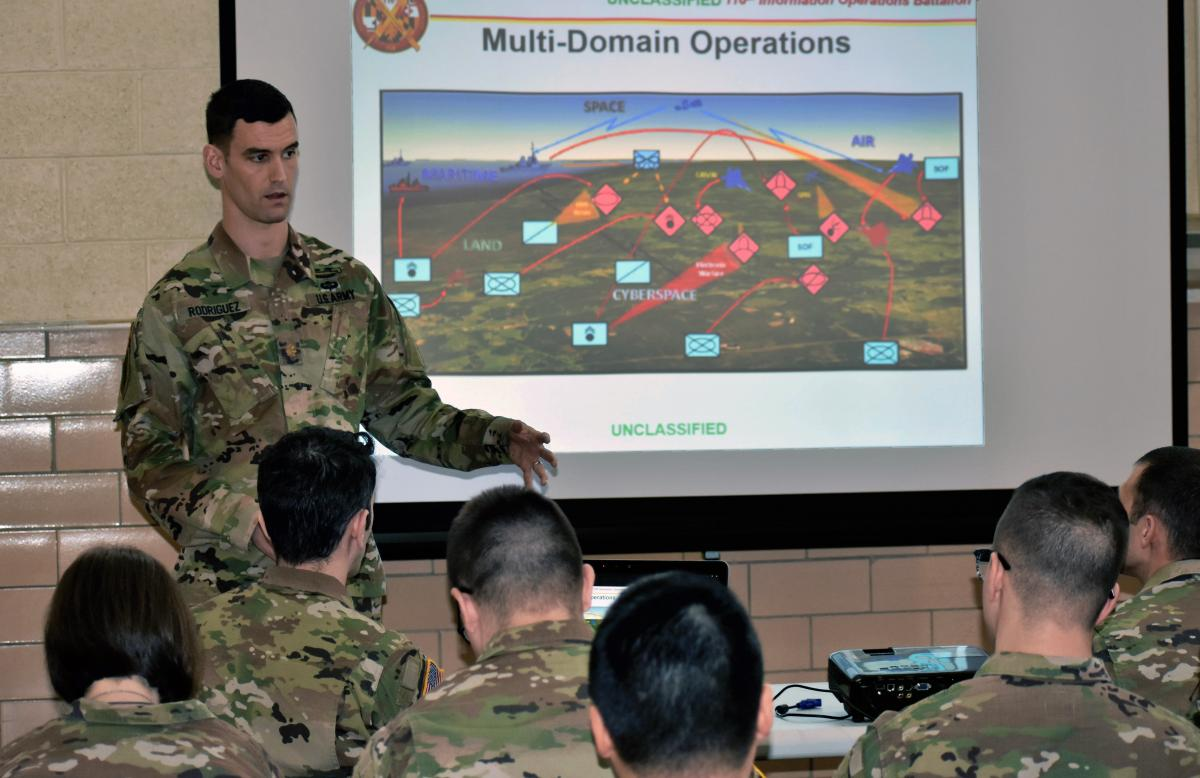 An Army IO officer briefs soldiers