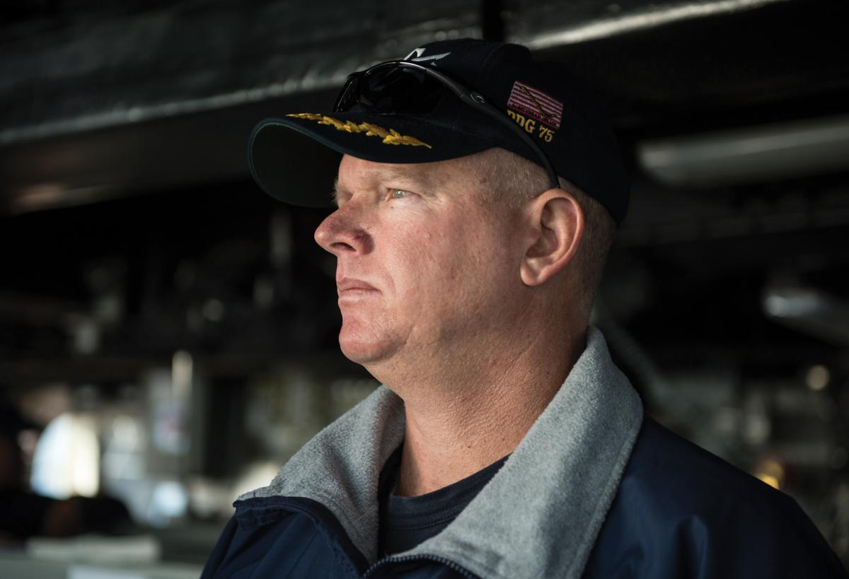 Commanding Officer of the USS Donald Cook (DDG-75) standing on the bridge.