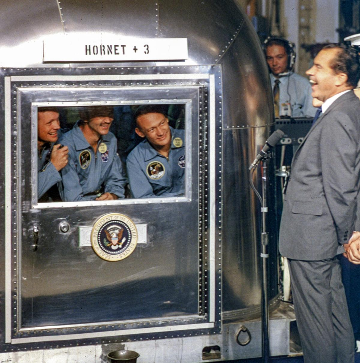 Astronauts in the Mobile quarantine facility aboard USS Hornet greet President Nixon
