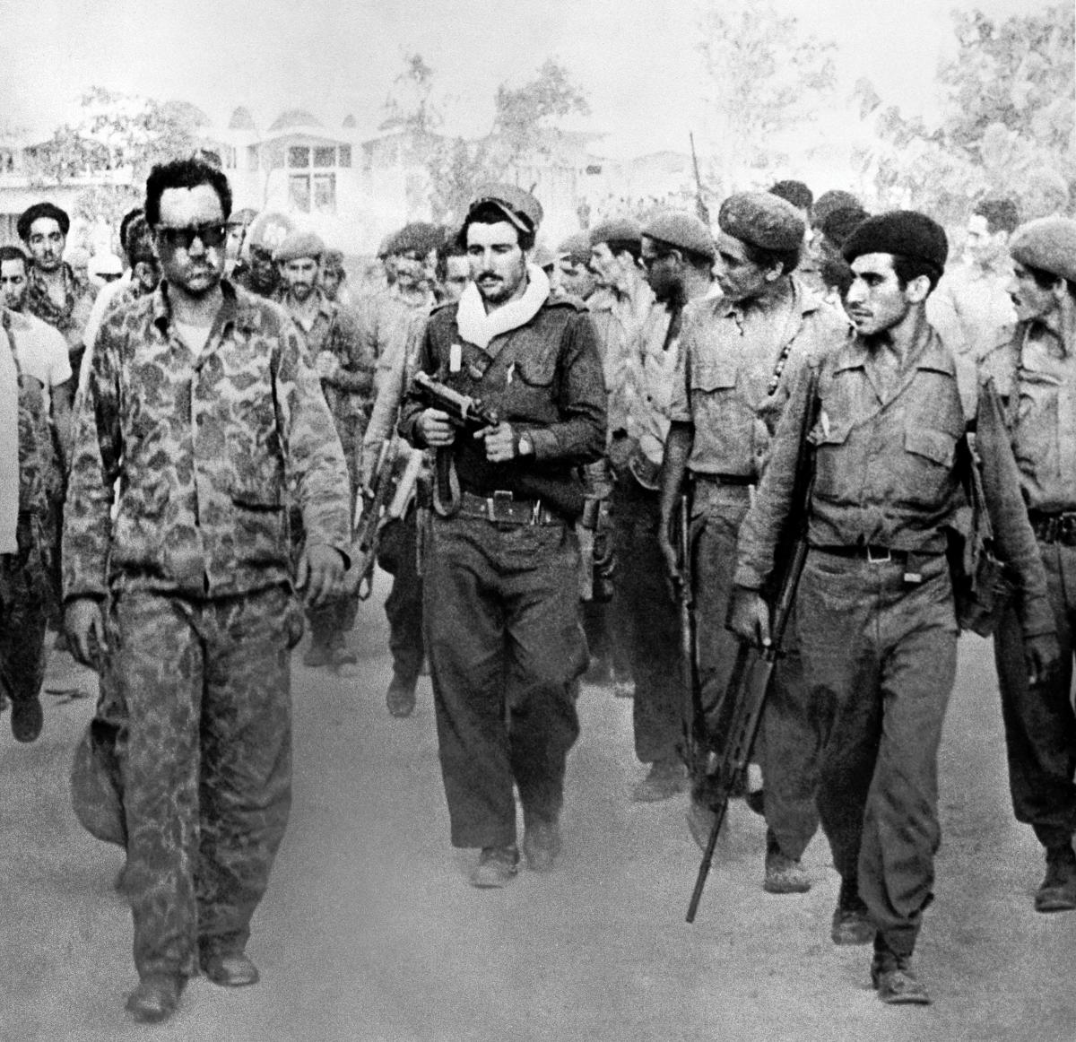 Cuban troops lead away a captive CIA officer (left) after the disastrous amphibious landing attempt at the Bay of Pigs.  The decision to hold off on air support, and the failure to make fuller use of the offshore U.S. fleet, sealed the undertaking's doom.