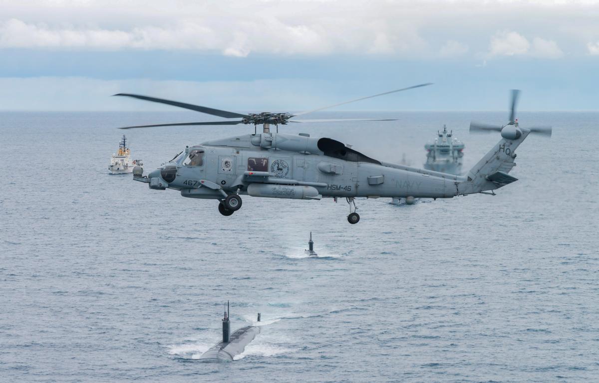 O helicóptero Navy Seahawk sobrevoa os submarinos USS Toledo e HNoMS Ures enquanto participa do Dynamic Mongoose