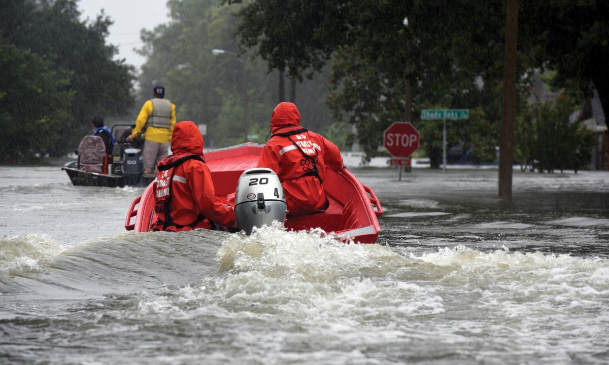 Coast Guardsmen pilot a 16-foot flood punt boat and join good Samaritans in patrolling a flooded neighborhood in Friendswood, Texas