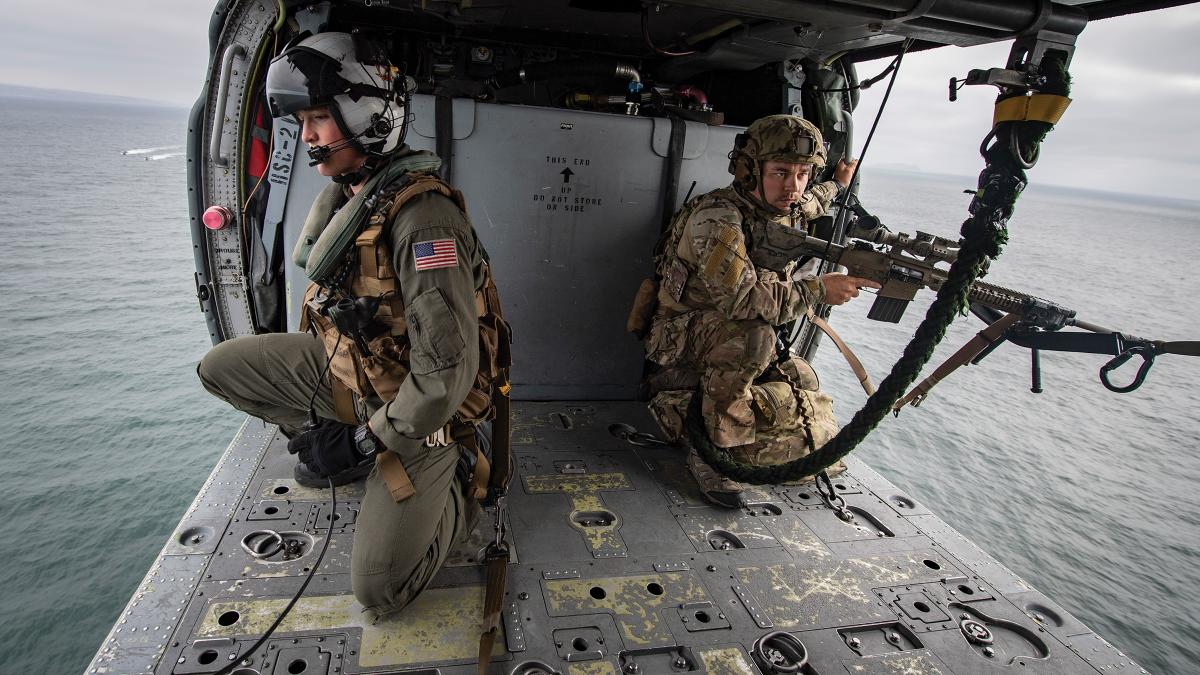 A naval aircrewman and Coast Guard precision marksman in the cabin of an MH-60 Seahawk helicopter from Helicopter Sea Combat Squadron 21 while training off the coast of San Diego. The combination of enduring long hours in cramped positions and vibrations unique to helicopters has made chronic back pain far more prevalent in naval helicopter aircrewmen.