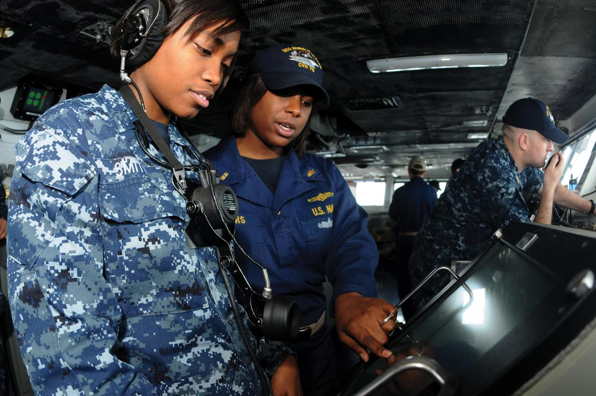 Chief Warrant Officer 2 Lashona Rodgers observes Operations Specialist Seaman Raven Smith as she stands watch on the bridge of the USS Ronald Reagan (CVN-76)