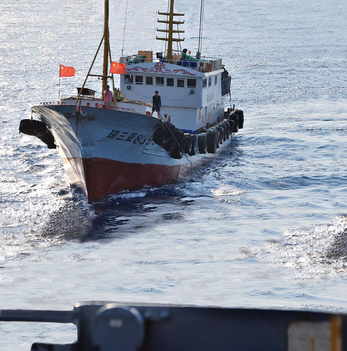 A crewmember on a Chinese trawler uses a grapple hook in an apparent attempt to snag the towed acoustic array of the military Sealift Command ocean surveillance ship USNS Impeccable (T-AGOS-23)