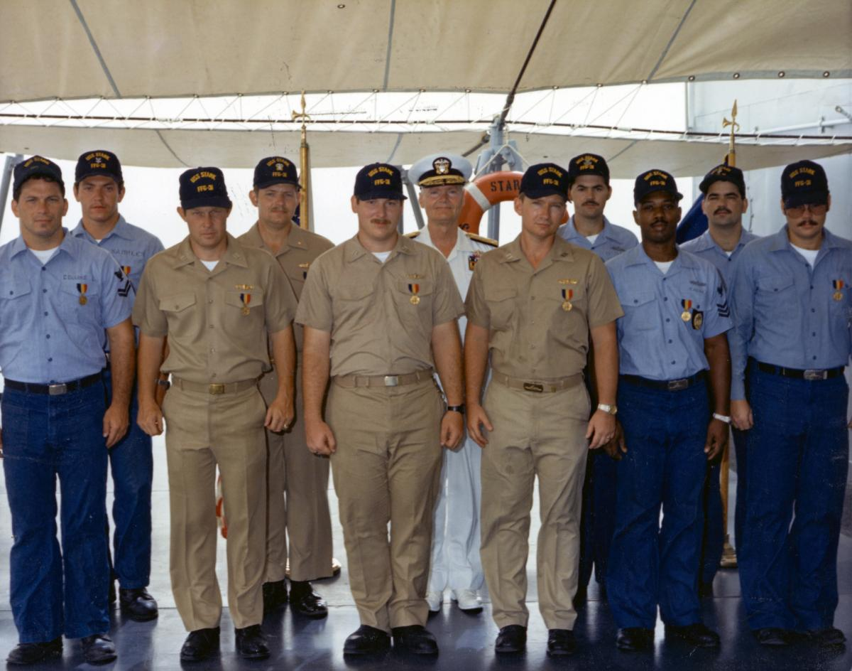 en crew members of the USS Stark (FFG-31) pose for a group photo after receiving the Navy and Marine Corps Medal for heroism.