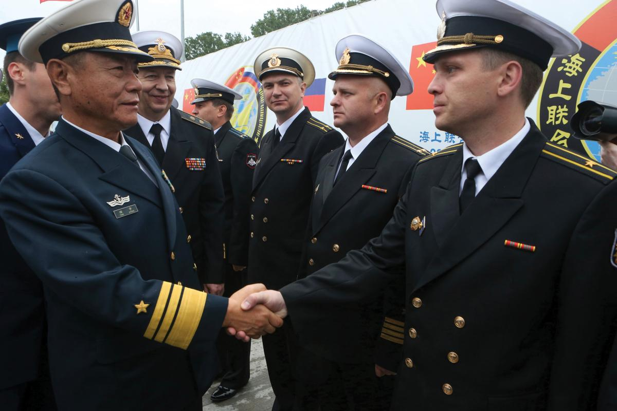 Chinese and Russian navy commanders greet each other