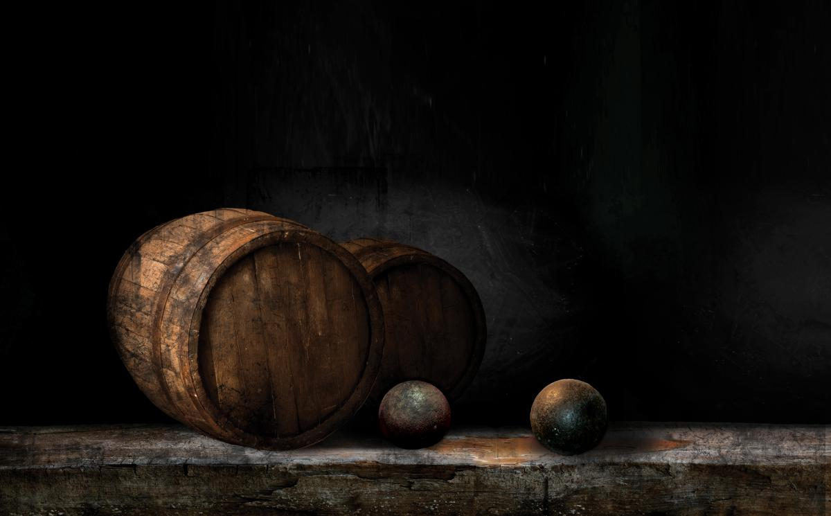 Stock photo of two cannon balls laying near a cask
