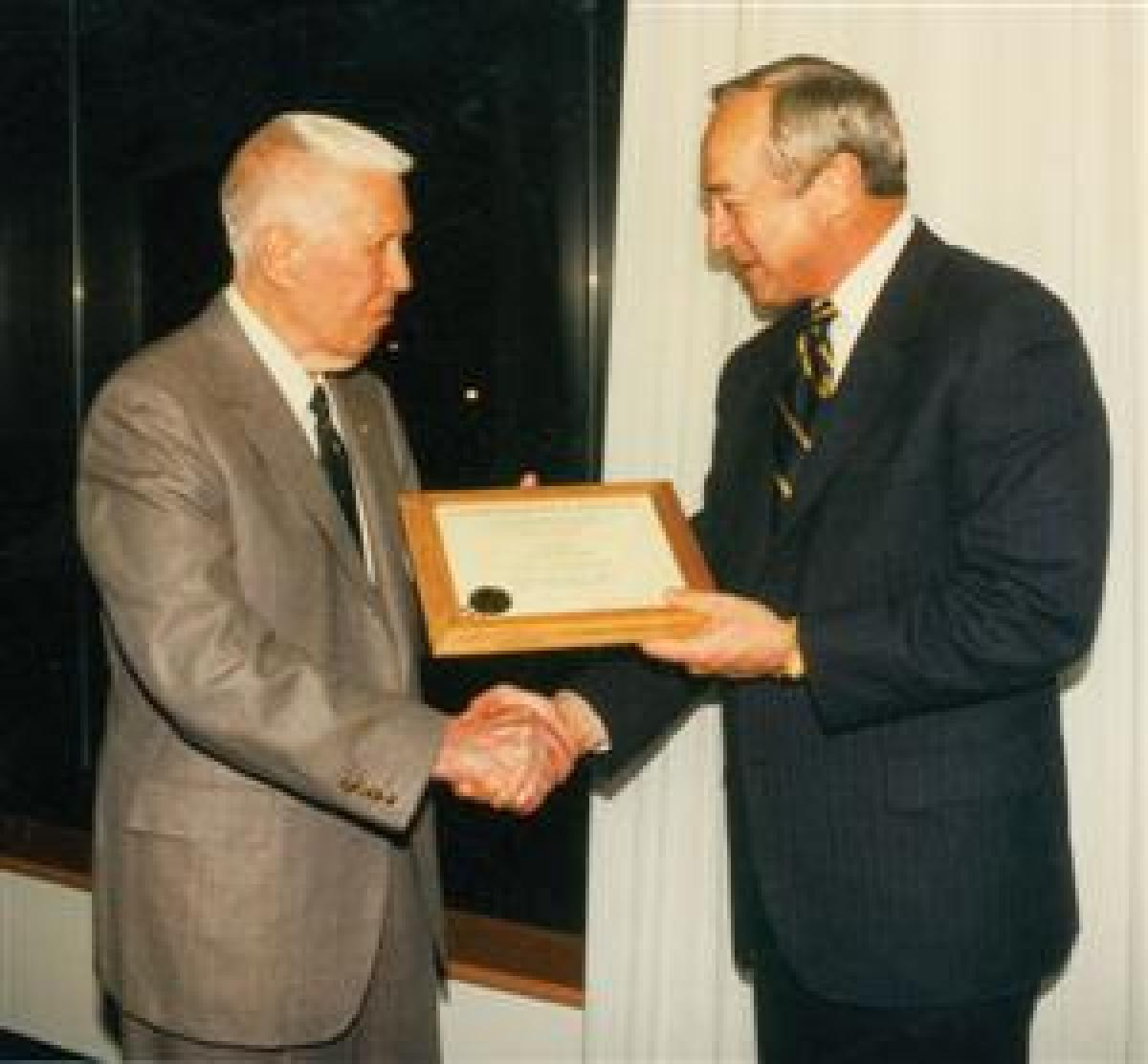 Secretary of the Navy John Dalton, right, congratulates Brast Thomas on becoming a Naval Institute Commodore in April 1996.
