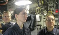 Female submariners standing at a control panel
