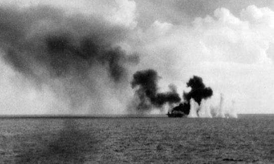 Shells from Japanese cruisers land near the burning escort carrier Gambier Bay during the Battle off Samar on the morning of 25 October 1944