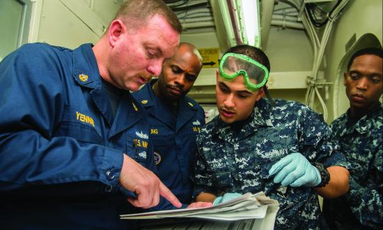 Chief Electronics Technician Douglas Yennie, a 3M supervisor, briefs sailors on the maintenance of the USS Harry S.  Truman (CVN-75).