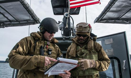 Chief Boatswain's mates review a drill guide during a Coastal Riverine navigational check ride