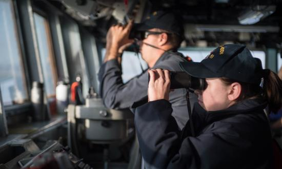 LTJG Lindsey Westfall looks through binoculars on the bridge aboard the guided-missile destroyer USS Chung-Hoon (DDG-93) as the ship pulls into Salalah, Oman.