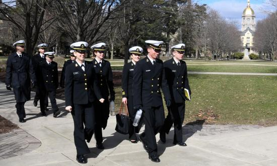 Notre Dame NROTC midshipmen walking past the iconic golden dome of the Basilica of the Sacred Heart.