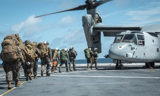 Marines prepare to load onto an MV-22 Osprey on board the USS John P. Murtha (LPD-26)