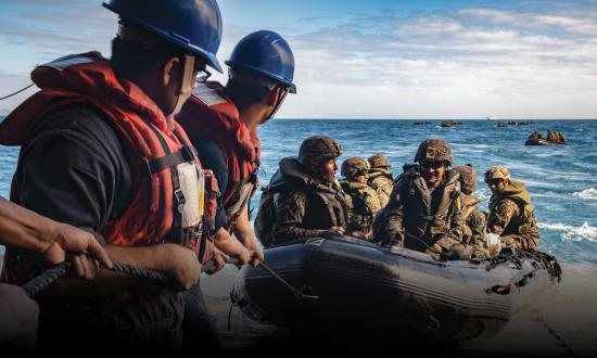 Sailors man a safety line as Marines with the 31st Marine Expeditionary Unit (MEU) stand fast on the stern gate during Combat Rubber Raiding Craft (CRRC) operations