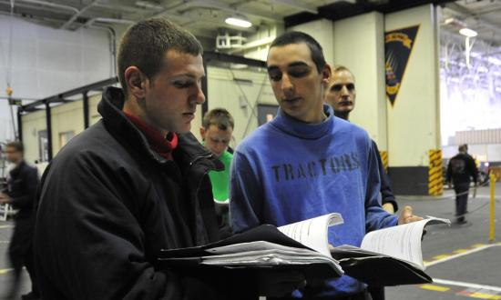 Two aviation boatswain's mates look through their PQS books