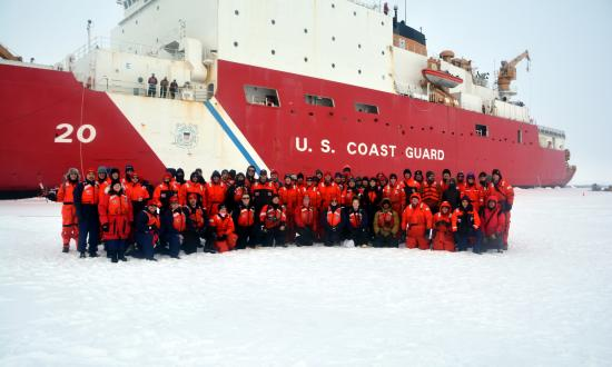 Coast Guard Cutter Healy (WAGB-20) crewmembers and scientists pose for a group photo during Healy's first ice station while deployed to the Arctic Ocean in 2019.