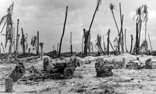 Marine packs and helmets hang from the barrel of a lone 37-mm gun on Tarawa