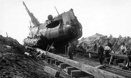 Starboard bow view of submarine USS H-3 on a wooden cradle after being beached.