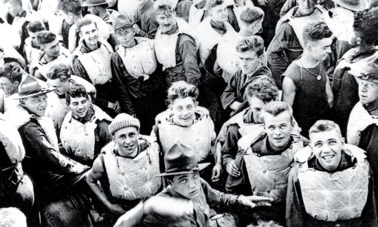 "Troops in life jackets crowd the main deck of the USS President Lincoln as she steams through the submarine ""danger zone"" in the Atlantic on 25 December 1917."