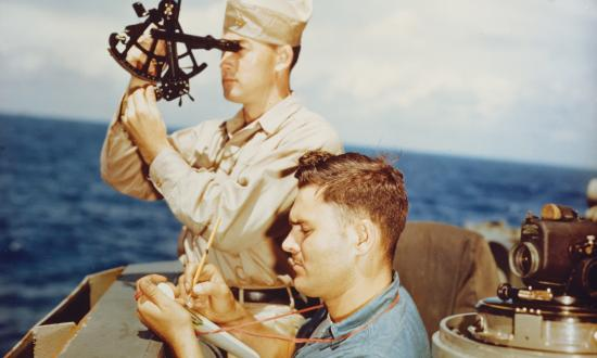 A quartermaster takes a sun sighting from the navigation bridge of the USS Alaska (CB-1) in 1945.