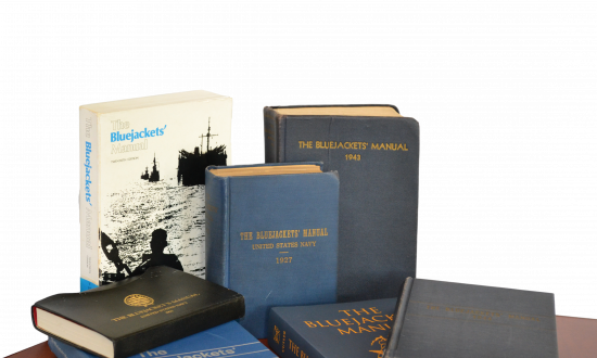 Seven different editions of the Bluejacket's Manual on a table