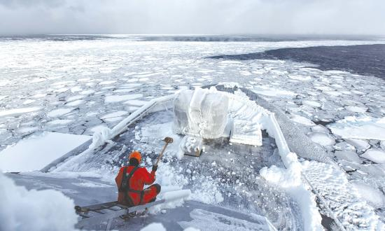 A coast guardsman chips ice on board the Royal Norwegian Coast Guard offshore patrol vessel NoCGV Svalbard.