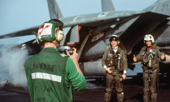 A squadron member photographs the pilot and radar intercept officer of a Fighter Squadron 74 (VF-74) F-14A Tomcat aircraft before they depart on a mission from the aircraft carrier USS SARATOGA (CV-60) during Operation Desert Storm