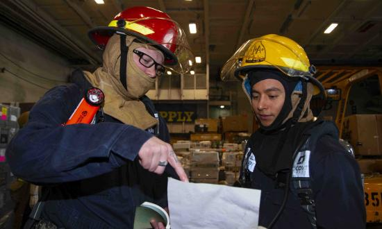 Navy Sailors plan a firefighting exercise onboard ship.