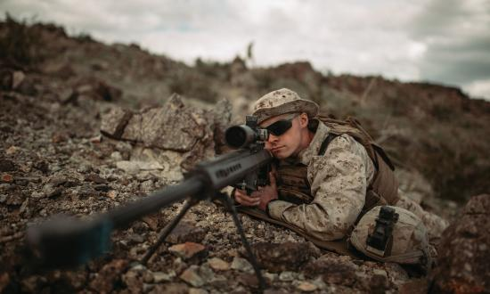 U.S. Marine Corps scout sniper looks down the scope of an M82 Special Applications Scoped Rifle