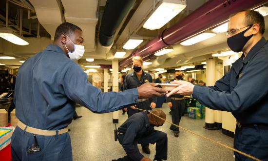 The USS Gerald R. Ford (CVN-78) command master chief hands out cake to sailors to commemorate the ship's three-year commissioning anniversary. The Ford's sailors are executing battle messing in spaces that accommodate six-foot social distancing.