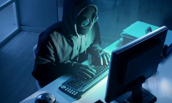 Masked hacker at a computer